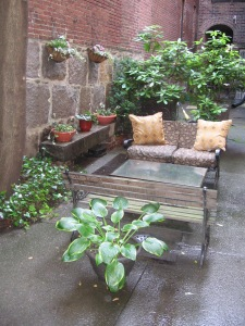 Photograph of a courtyard arranged with beautiful foliage and blooming plants